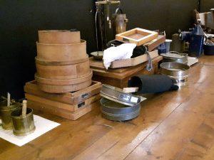 inhoud vitrinekasten Graanmuseum Woldzigt uitgestald op de vloer